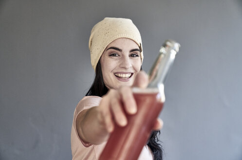Portrait of smiling young woman holding bottle - FMKF04023
