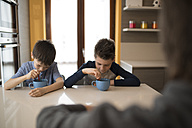 Two boys eating side by side at kitchen table - ZOCF00211