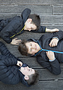 Three friends wearing black hooded jackets lying together on terrace - ZOCF00217
