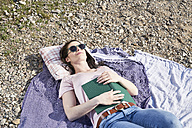 Young woman lying on blanket with book - FMKF04048