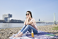 Germany, Cologne, young woman relaxing at River Rhine - FMKF04054