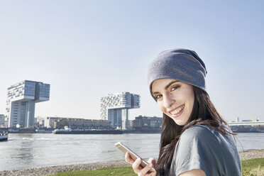Germany, Cologne, portait of smiling young woman using cell phone at River Rhine - FMKF04063