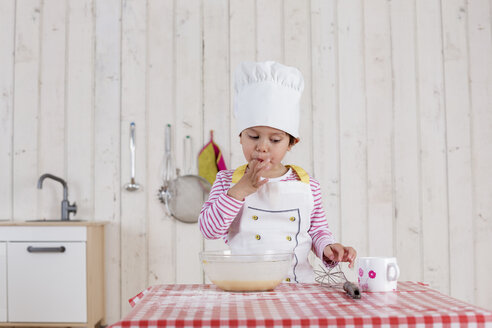 Little girl preparing waffles, wearing chef's hat - DRF01723