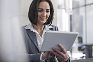 Businesswoman holding digital tablet in office - ZEF13592