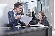 Businessman talking to woman in office - ZEF13598