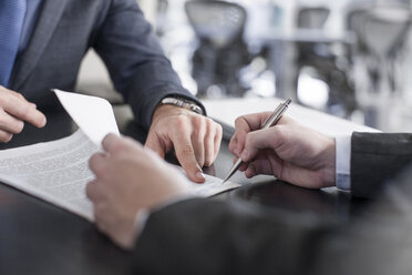Businessman showing client where to sign document - ZEF13610