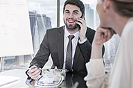 Businessman on a call in office during lunch - ZEF13628