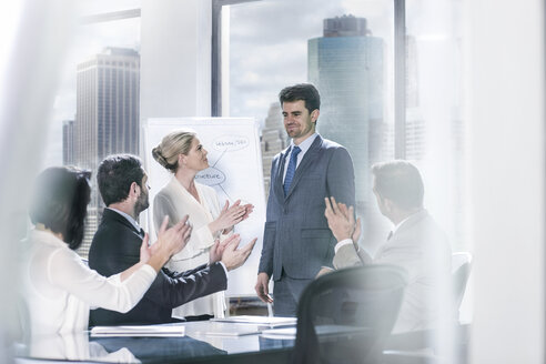 Group of businesspeople clapping hands after a presentation in city office - ZEF13631