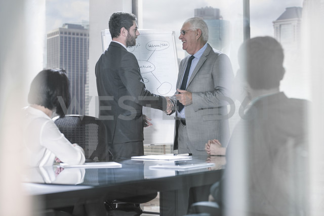 Two businessmen shaking hands at office meeting - ZEF13634