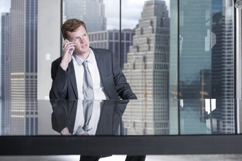 Businessman on the phone at desk in city office - ZEF13652