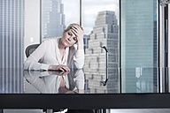 Serious businesswoman sitting at desk in city office - ZEF13661