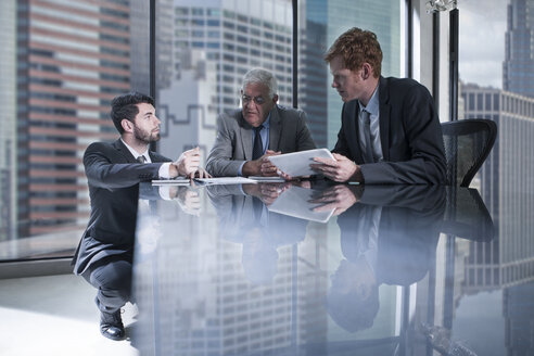 Three businessmen with tablet and documents discussing in office - ZEF13664