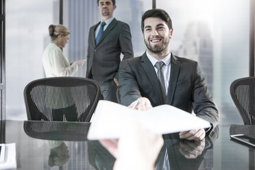 Businessman receiving paper in city office - ZEF13667