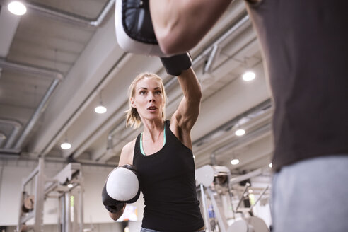 Young woman boxing with her coach - HAPF01546