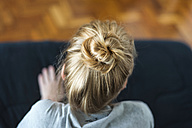 Woman with ginger hair bun sitting on sofa - VABF01334