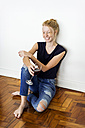 Ginger woman sitting on floor at home, drinking red wine - VABF01337