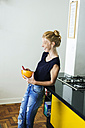 Ginger woman standing in kitchen eating breakfast - VABF01340