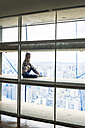 Young woman in high rise building sitting in window, looking over city - VABF01349