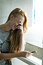Young woman holding smartphone, laughing - VABF01352