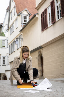 Germany, Tuebingen, young woman collecting documents on the street - MIDF00827