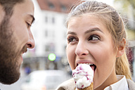 Portrait of young woman eating ice cream with her boyfriend - MIDF00830