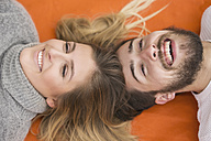 Portrarit of laughing couple lying head to head on blanket - MIDF00836