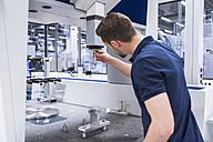 Man adjusting machine in testing instrument room - DIGF02143