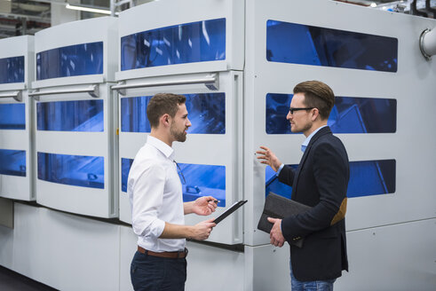 Two men talking in factory shop floor - DIGF02155