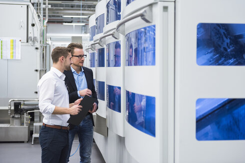 Two men talking in factory shop floor looking at machine - DIGF02158
