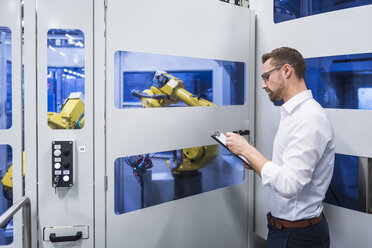Man taking notes at robotics machine in factory shop floor - DIGF02167