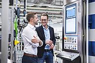 Two smiling men talking in factory shop - DIGF02179
