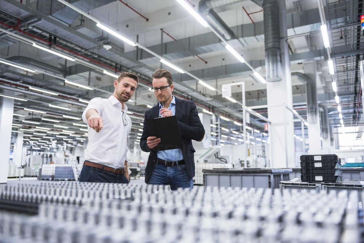 Two men talking in factory shop floor - DIGF02188 - Daniel Ingold/Westend61