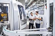 Two men talking at machine in factory shop floor - DIGF02194