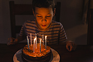 Boy blowing out burning candles on his birthday cake - NMSF00057