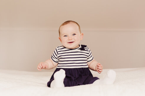 Portrait of smiling baby girl sitting on bed - NMSF00060