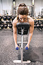 Young woman exercising with dumbbells in gym - HAPF01574