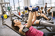Young woman exercising with dumbbells in gym - HAPF01577