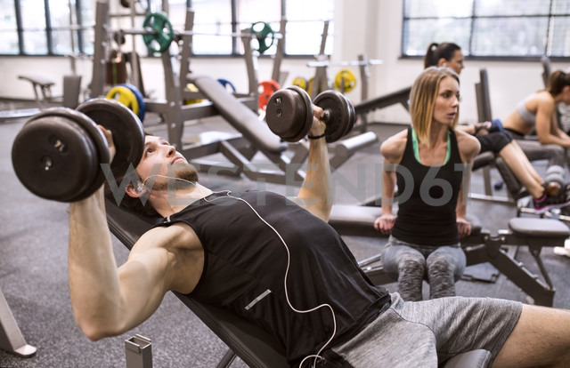 Young man exercising with dumbbells in gym - HAPF01580