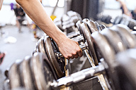 Young woman taking dumbbell - HAPF01583