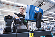 Man with wearable scanner on tugger train in factory shop floor - DIGF02211