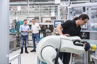Man operating assembly robot in factory with two men in background supervising - DIGF02241