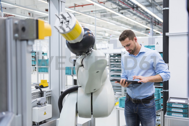 Man using tablet nextb to assembly robot in factory shop floor - DIGF02250 - Daniel Ingold/Westend61