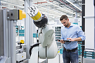 Man using tablet nextb to assembly robot in factory shop floor - DIGF02250