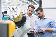 Two men with tablet examining assembly robot in factory shop floor - DIGF02253