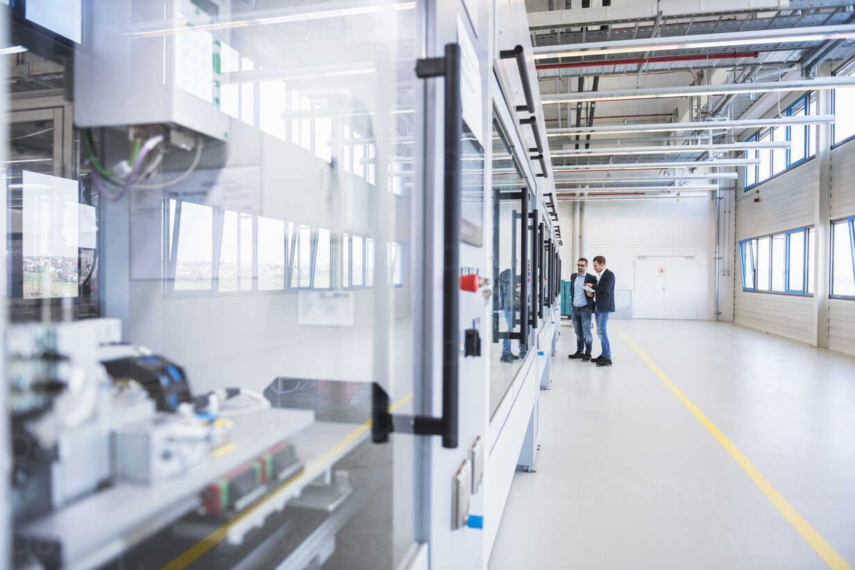 Two men with tablet talking in factory shop floor - DIGF02256 - Daniel Ingold/Westend61
