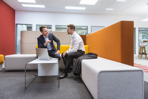 Businessmen sitting in conversation pit, discussing in front of laptop - DIGF02280