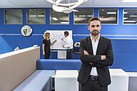 Businessman standing in conference room, while colleagues working with flipchart in background - DIGF02286