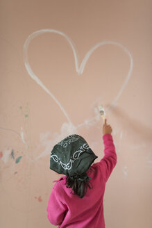 Back view of little girl painting heart on wall of children's room - JASF01770