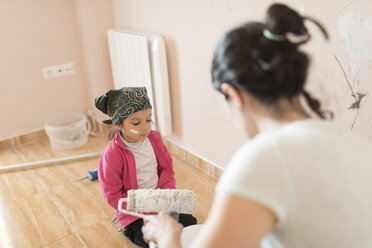 Mother and daughter painting wall in children's room - JASF01773