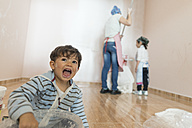 Portrait of screaming little boy painting painting together with mother and sister - JASF01779